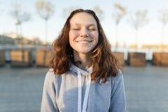 Портрет счастливой предназначенной для подростков девушки с глазами закрыл, золотой час стоковое фото rf