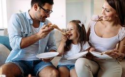 Портрет счастливой семьи деля пиццу дома стоковые фотографии rf