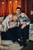 Портрет счастливой семьи обнимая в украшенной студии стоковое фото rf