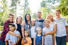 Портрет счастливой семьи 11 представляя в парке Стоковое Фото
