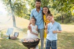 Портрет счастливой семьи при 2 дет стоя outdoors около барбекю Стоковые Фотографии RF
