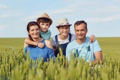 Портрет счастливой семьи сидя на природе в траве Стоковые Фотографии RF