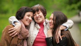 Портрет счастливой симпатичной семьи в парке Усмехаясь сестры обнимают их мать Outdoors