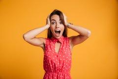 Портрет счастливой удивленной молодой женщины в красном платье стоя wi Стоковые Фотографии RF