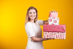 Портрет счастливой усмехаясь девушки в платье показывает присутствующие коробки над желтой предпосылкой стоковые изображения rf