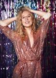 Портрет счастливой усмехаясь девушки в стильном блестящем платье с sequins на партии моды стоковая фотография rf
