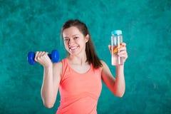 Портрет счастливой усмехаясь молодой женщины в носке фитнеса с бутылкой воды и гантелей, над предпосылкой бирюзы Стоковая Фотография RF
