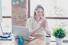 Портрет счастливой усмехаясь радостной секретарши который печатая sms на ее s стоковые фотографии rf