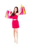 портрет счастливой excited азиатской женщины в красном платье стоя и держа сумка цвета бумажная Стоковые Фото