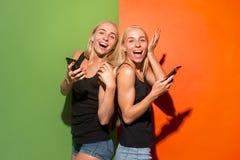 Портрет счастливые усмехаясь вскользь девушки с мобильными телефонами над предпосылкой студии стоковые изображения