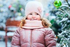 Портрет счастливый идти ребёнка внешний в снежном дне, город зимы и рождества украшенный на праздники стоковая фотография rf