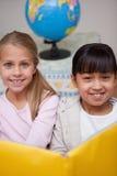 Портрет счастливый читать школьниц Стоковое Изображение