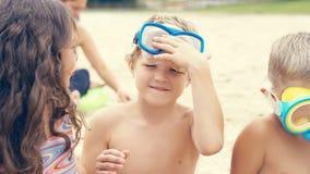 Портрет счастливых детей с маской заплывания на голове играя на пляже моря стоковое изображение