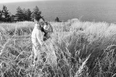 Портрет счастливых красивых пар на природе с большим озером Молодые пары обнимая на береге реки или море Человек обнимая красные  стоковая фотография rf