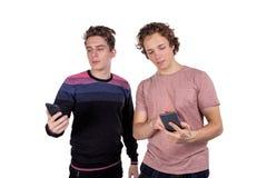 Портрет 2 счастливых молодые люди используя мобильные телефоны изолированные над белой предпосылкой стоковые фотографии rf