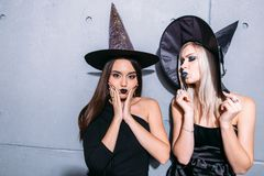 Портрет 2 счастливых молодых женщин в черных костюмах хеллоуина ведьмы на партии Стоковые Изображения RF
