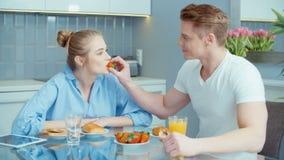 Портрет счастливых молодых пар говоря и смеясь над во время завтрака дома видеоматериал