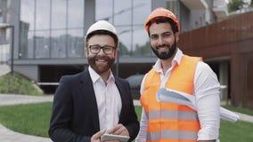 Портрет счастливых построителя и бизнесмена смотря положение камеры против фона современного здания акции видеоматериалы