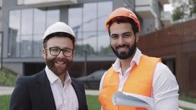 Портрет счастливых построителя и бизнесмена смотря положение камеры против фона современного здания сток-видео