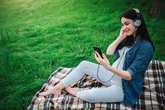Портрет счастливых черных волос и гордой беременной женщины в городе на заднем плане Она сидит на стенде города стоковое изображение
