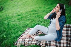 Портрет счастливых черных волос и гордой беременной женщины в городе на заднем плане Она сидит на стенде города стоковое фото rf