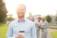 Портрет счастливого бизнесмена держа устранимую чашку при коллеги стоя в предпосылке Стоковые Фотографии RF