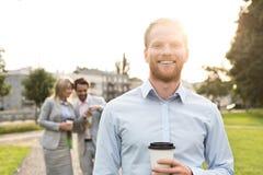 Портрет счастливого бизнесмена держа устранимую чашку при коллеги стоя в предпосылке Стоковые Фото