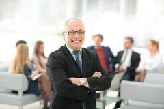 Портрет счастливого бизнесмена при коллеги взаимодействуя на ба Стоковые Фотографии RF