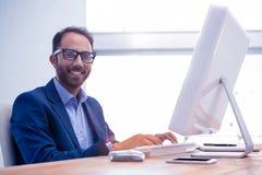 Портрет счастливого бизнесмена работая на компьютере в офисе Стоковые Фото