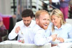 Портрет счастливого бизнесмена сидя с коллегами на внешнем ресторане Стоковые Изображения