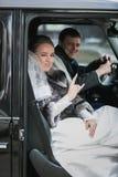 Портрет счастливого жениха и невеста представляя в автомобиле Стоковая Фотография RF