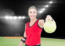 Портрет счастливого женского игрока гандбола держа шарик на суде гандбола Стоковое фото RF