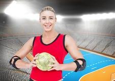 Портрет счастливого женского игрока гандбола держа шарик с стадионом в предпосылке Стоковое Изображение RF