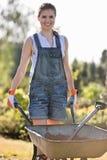 Портрет счастливого женского садовника нажимая тачку на саде Стоковые Изображения RF