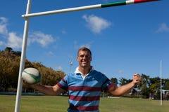 Портрет счастливого игрока рэгби держа шарик против голубого неба Стоковые Изображения RF