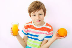 Портрет счастливого мальчика выпивая апельсиновый сок стоковые изображения