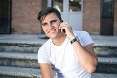 Портрет счастливого молодого бизнесмена используя мобильный телефон вне офиса Стоковая Фотография RF