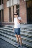 Портрет счастливого молодого бизнесмена используя мобильный телефон вне офиса Стоковое Изображение RF