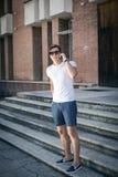 Портрет счастливого молодого бизнесмена используя мобильный телефон вне офиса Стоковое Изображение