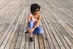Портрет счастливого молодого красивого афро американского усаживания женщины Стоковые Изображения