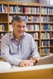 Портрет счастливого профессора сидя на столе используя компьтер-книжку стоковая фотография