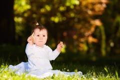 Портрет счастливого ребенка сидя на луге и закуске владениями в парке Стоковое фото RF