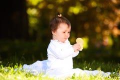 Портрет счастливого ребенка сидя на луге и закуске владениями в парке Стоковое Изображение RF