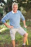 Портрет счастливого садовника при инструмент стоя на саде Стоковая Фотография