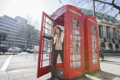 Портрет счастливой двери отверстия молодой женщины переговорной будки на Лондоне, Англии, Великобритании Стоковое Изображение