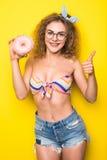 Портрет счастливой девушки битника с donuts одним и одобренные подписывают сверх желтую предпосылку Стоковая Фотография