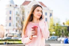 Портрет счастливой девушки говоря на телефоне и выпивая кофе на солнечной улице города Стоковая Фотография