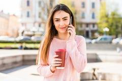 Портрет счастливой девушки говоря на телефоне и выпивая кофе на солнечной улице города Стоковые Фото