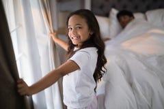 Портрет счастливой девушки держа занавесы в спальне Стоковое Изображение RF
