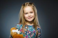 Портрет счастливой девушки играя при собака игрушки изолированная на сером цвете Стоковые Изображения RF